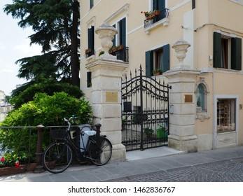 Adria, Italy - June 13, 2019. Ponte Castello, bridge. Old villa, wayside shrine and bike.