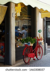 Adria, Italy - June 13, 2019. Red bicycle in front of a baker's window.