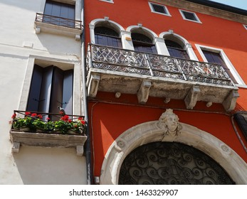 Adria, Italy - June 13, 2019. Ancient red palace in Venetian style. Next to it is a window with flowers.