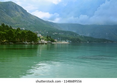 Adriatic coast in the Dalmatian part of Croatia, with mountains and houses on the shoreline of the Adriatic sea, during a cloudy afternoon