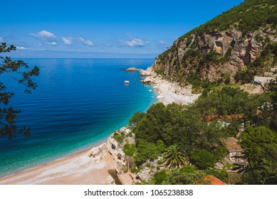 Adriatic sea coast by sunny day summer Montenegro landscape. Pebble beach, house roofs and green tree brunches under blue sky near Perazica Do village on the way to Petrovac.