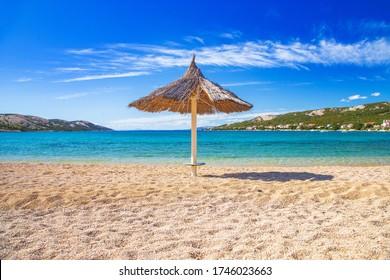Adriatic sea shore in Croatia on Pag island, parasol on beautiful Puntica sand beach