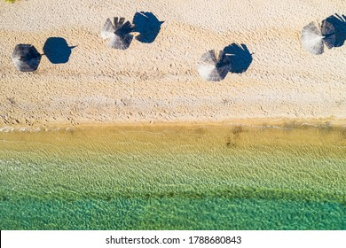 Adriatic sea shore in Croatia on Pag island, beautiful sand beach with parasols, aerial overhead view