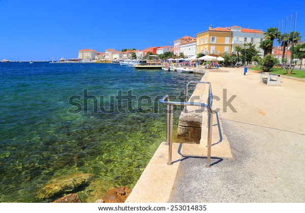 Adriatic sea shore and distant town and harbor of Porec, Croatia
