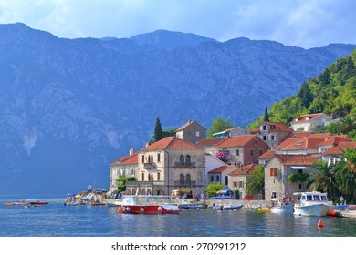 Adriatic sea surrounding traditional buildings of an old Venetian town in front of the mountains, Perast, Montenegro