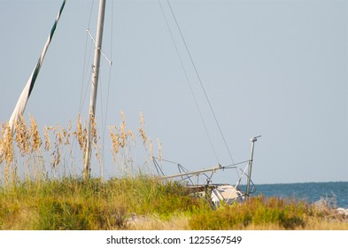 Adrift sailboat beached on the shoreline.