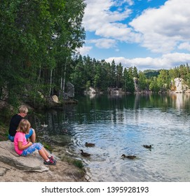 Adrspach, Czech Republic - August 16, 2018: Mother and daughter feeding ducks on lake in rock city Adrspach, National park of Adrspach, Czech Republic
