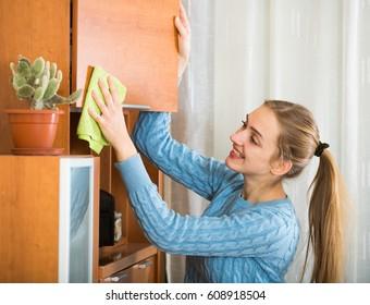 Aduiltl girl in blue jersey dusting shelves at home