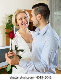 Adult american son asking senior mother to dance at home