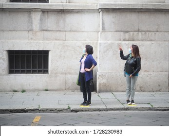 adult asian female  and adult caucasic woman wearing sterile protective facial mask and gloves, making stop it there sign gesture to the  driver at the bus stop at the proper social distancing