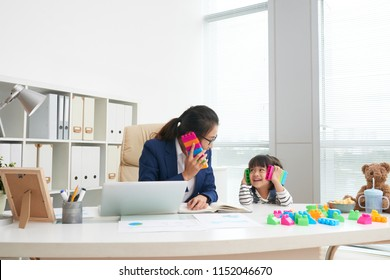 Adult Asian formal businesswoman with playful little girl sitting at table in modern office having fun with colorful blocks