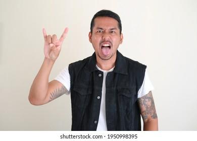Adult Asian man doing rockstar pose. Sticking tongue out