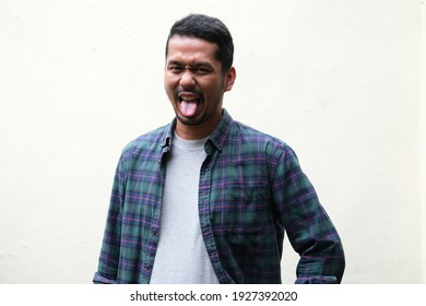 Adult Asian man stick out his tongue with funny expression