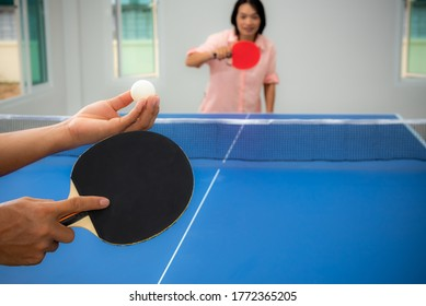 Adult Asian woman are waiting to start playing table tennis or Ping pong indoor. Leisure with competing in sports games in the house, Recreation or exercise stay at home with the family in Thailand