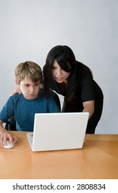 An adult assists a child using a laptop computer.