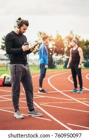 Adult athlete man using mobile phone and listen music after outdoor running workout