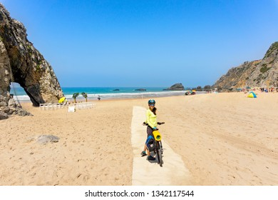 Adult attractive female cyclist  with her bike  is posing and smiling on a ocean beach.