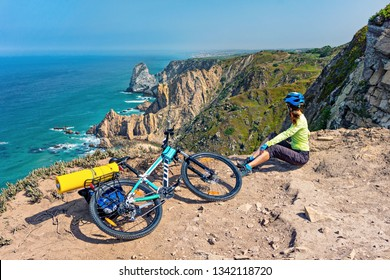 Adult attractive female cyclist  with her mountain bike  sits on a ocean rocky coast.  Cape Roca, Portugal, Europe.