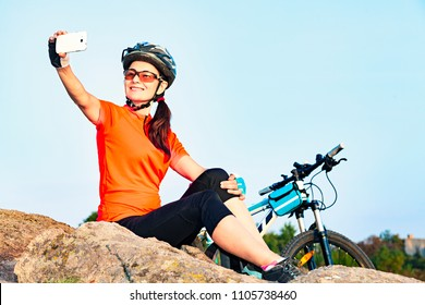Adult attractive female cyclist on relaxation taking a selfie photo outdoor.