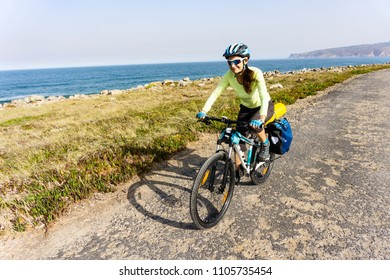 Adult attractive female cyclist  rides her mountain bike along the ocean shore. Europe. Portugal.