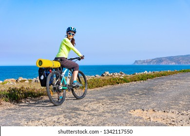 Adult attractive female cyclist riding her mountain bike by the ocean coast and looking back at the camera. Portugal, Europe.