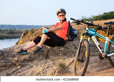Adult attractive female cyclist sitting on the rock and resting.