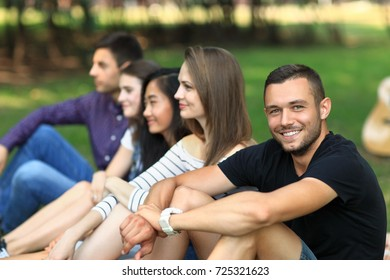Adult attractive friends having fun on open air. Focus on handsome man smiling and looking at camera. Cheerful friends company spending free time outdoors