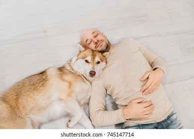 Adult bald man with husky puppy sleeping on floor. Owner with pet together at home. Kind and soulful emotions. Lovely dog resting with young male. Guy with beloved domestic animal hugging each other.