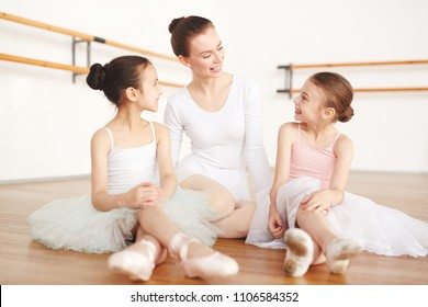 Adult ballerina sitting in light room with girls in white clothes and pointe in dancing studio