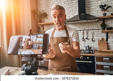 Adult bearded chef standing on the kitchen while filming himself for blog. Mature man explaining a recipe for baking a pie and holding berries in hands while looking at the phone camera. Live stream