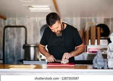 Adult bearded man in black apron slicing fish liver at counter in street food truck
