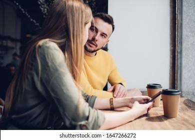 erwachsener Bärenmann in ungezwungenen Kleidern, die unerkennbare Frau in grünem Shirt mit Smartphone anschauen, während er am Tisch sitzt, um heißes Getränk in der Nähe des Fensters zu trinken und sich im Café unterhalten