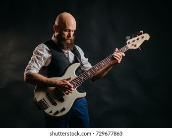 adult bearded man enthusiastically playing guitar on a black background