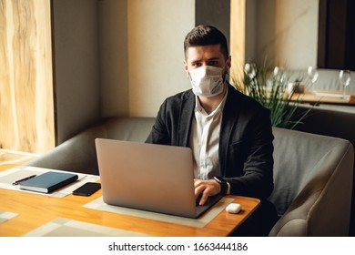 Adult bearded man indoors in cafe. Lifestyle concept photo with copy space. Picture of professional with disposable protective face mask and gray personal computer