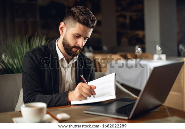 Adult bearded man indoors in cafe. Lifestyle concept photo with copy space. Picture of professional with notebook and laptop