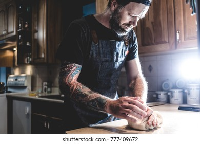 Adult bearded man kneading and preparing dough with pretzels on kitchen.