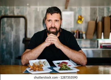 Adult bearded man leaning on hands at counter in food truck with served exotic food looking at camera