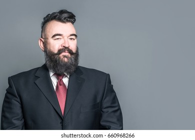 Adult bearded man in a suit on a gray background