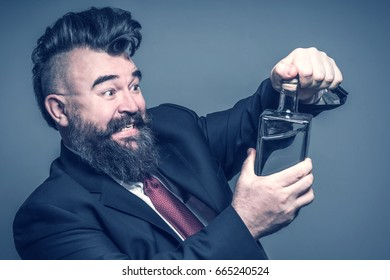 Adult bearded man in suit pulling out the cork from a bottle with alcohol