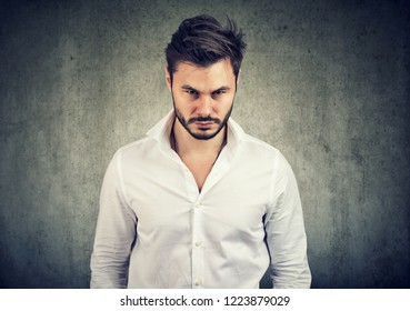 Adult bearded man in white shirt looking with anger and offense at camera on gray background