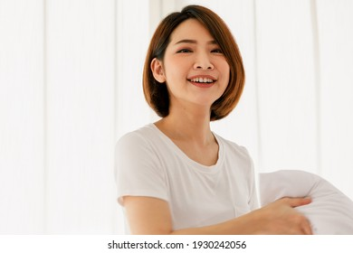 Adult beautiful asian woman pretty with short brown hair and wearing white t-shirt holding white pillow smiling and happy casual in morning on one day.