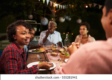 Adult black family eat dinner in garden, over shoulder view