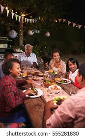 Adult black family enjoy dinner together in garden, vertical