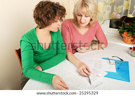 Adult blond woman and young woman discussing documents