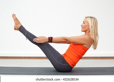 Adult blonde woman performing boat pose, lifting legs, indoors