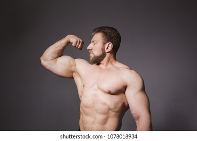 adult bodybuilder with pumped muscles posing on white cyclorama. short haircut and beard on the face. a surgical scar on the abdomen. dressed in tight leggings. emotional portrait of a fitness trainer