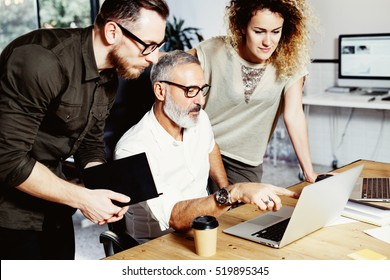 Adult boss and his assistant making great brainstorming in modern office.Bearded successful businessman talking with colleague about startup project.Business people discussion concept.Vertical.