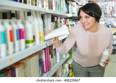 Adult brunette selecting the bottle of shampoo at the beauty store