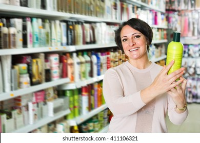 Adult brunette selecting a bottle of shampoo at a beauty store