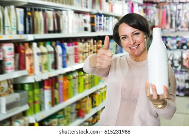 Adult brunette selecting a bottle of shampoo at the beauty store